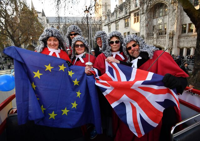Members of the pro-European movement Britain for Europe pose on a double decker bus dressed as judges outside the Supreme court building in London on the first day of a four-day hearing on December 5, 2016.
