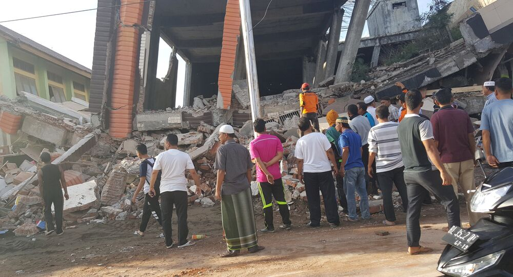 People survey the damage after dozens of buildings collapsed following a 6.4 magnitude earthquake in Ule Glee, Pidie Jaya in the northern province of Aceh, Indonesia December 7, 2016.