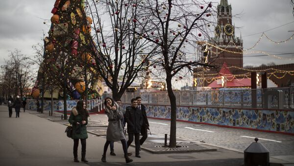 Young tourists enjoy a warm weather walking in Red Square illuminated to mark the upcoming Christmas and New Year celebrations in Moscow, Russia - Sputnik International