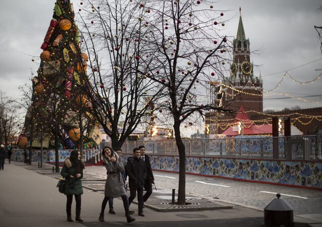 Young tourists enjoy a warm weather walking in Red Square illuminated to mark the upcoming Christmas and New Year celebrations in Moscow, Russia