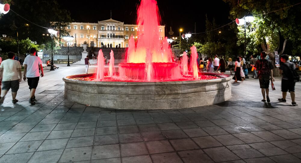 People walk near the fountain at Syntagma Square in front of the Greek Parliament in central Athens on July 4, 2015.