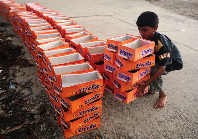 A Bangladeshi child lifts shoe boxes at a factory in Dhaka on August 7, 2012.