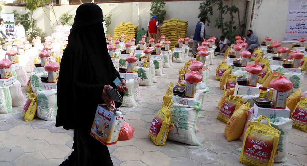 A Yemeni woman affected by the country's ongoing conflict walks past food rations provided by an initiative organised by a local charity in the capital Sanaa on June 2, 2016.