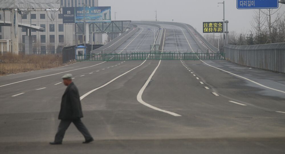 A man walks past the new Yalu Bridge in Dandong. The Chinese side of the bridge is finished, but construction on the Korean side has been halted due to a shortage of funds.