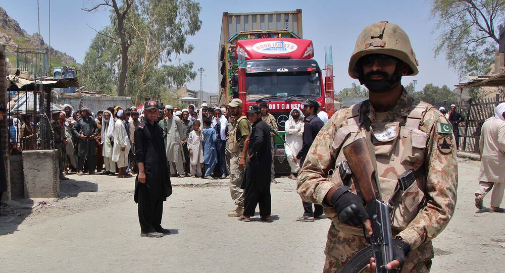 A Pakistani soldier stands guard as a truck enters Pakistan from Afghanistan at the border crossing in Torkham