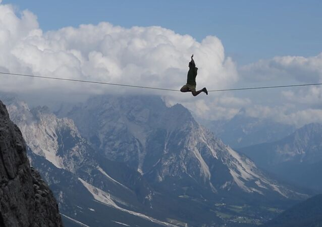 Guy Walks on Tightrope Between Mountains