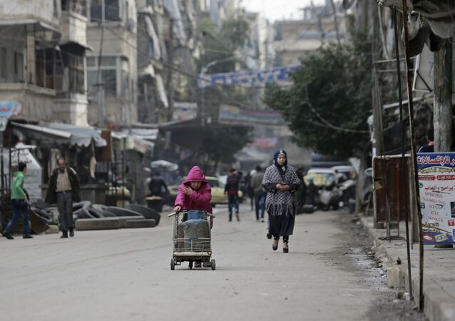 Syrian girl pushes a cart loaded with cooking gas canisters, in Aleppo, Syria.