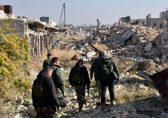 Syrian pro-government forces walk amidst the rubble in old Aleppo's Jdeideh neighbourhood on December 9, 2016