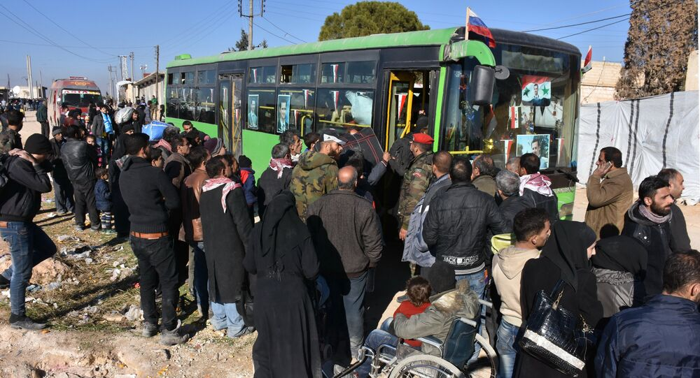 Syrian residents fleeing the violence, queue as they board a bus at a checkpoint, manned by pro-government forces, in the village of Aziza on the southwestern outskirts of the northern Syrian city of Aleppo on December 9, 2016