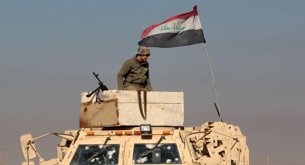 An Iraqi soldier stands atop an armoured vehicle