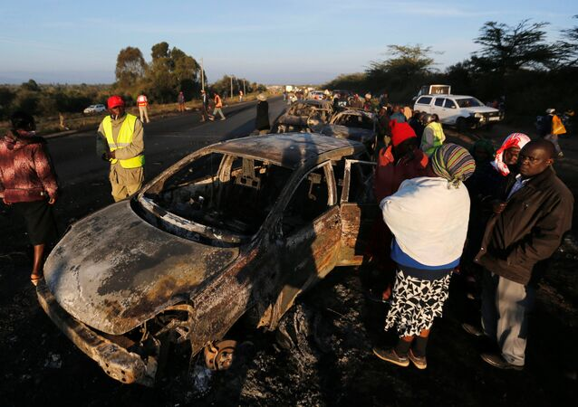 Relatives and civilians look at the wreckages of car burnt after a fireball from an tanker engulfed several vehicles and killed several people, near the Rift Valley town of Naivasha, west of Kenya's capital Nairobi, December 11, 2016