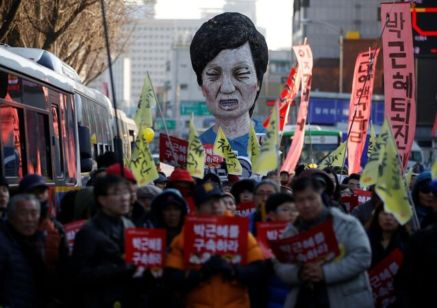 An effigy of South Korean President Park Geun-hye is seen behind people marching towards the Presidential Blue House during a protest calling for South Korean President Park Geun-hye to step down in central Seoul, South Korea, December 10, 2016