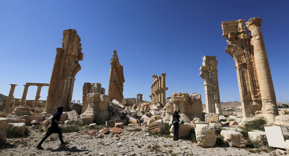 Journalists walk near the remains of the Monumental Arch in the historical city of Palmyra, in Homs Governorate, Syria April 1, 2016