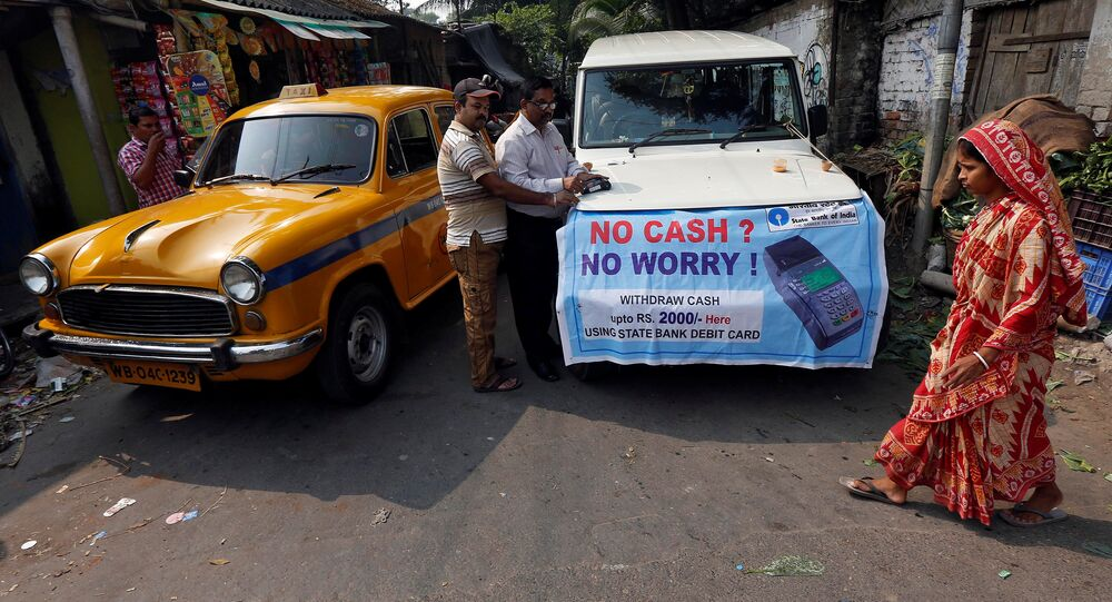 A bank officer swipes an ATM card of a man withdrawing Indian rupee banknotes at a mobile ATM van on the outskirts of Kolkata, India, November 24, 2016