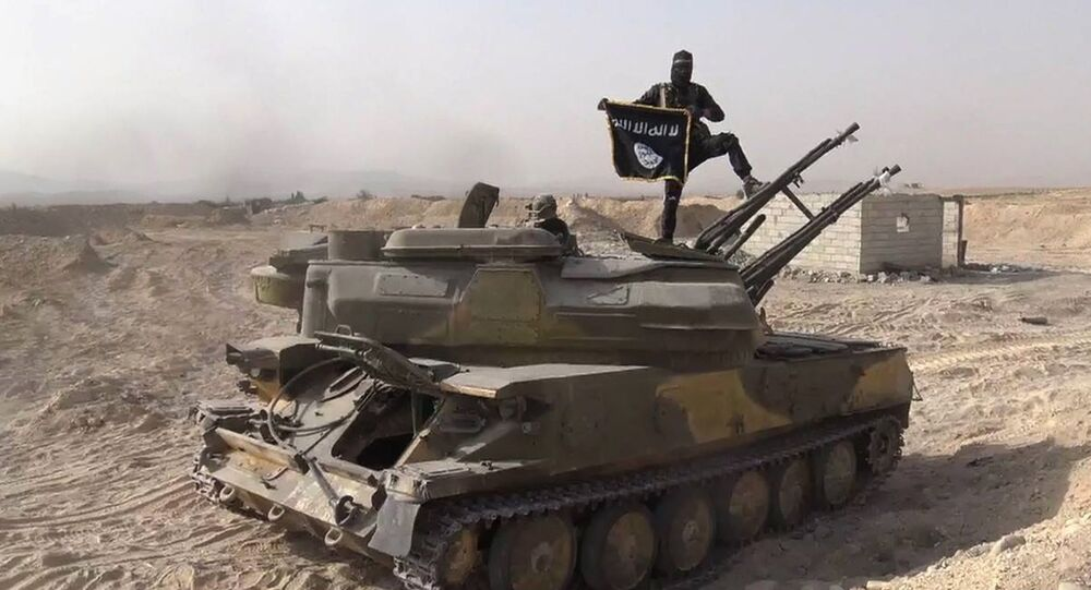 A Daesh terrorist holds Daesh's flag as he stands on a tank they captured from Syrian government forces, in the town of Qaryatain southwest of Palmyra, central Syria. file photo