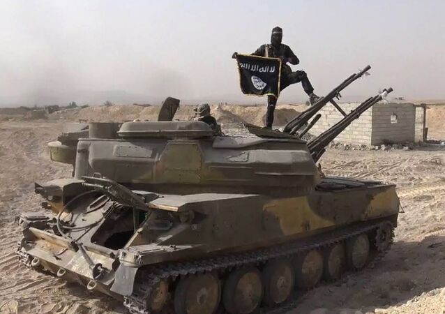 In this file photo released on Aug. 5, 2015, by the Rased News Network a Facebook page affiliated with Islamic State militants, an Islamic State militant holds the group's flag as he stands on a tank they captured from Syrian government forces, in the town of Qaryatain southwest of Palmyra, central Syria