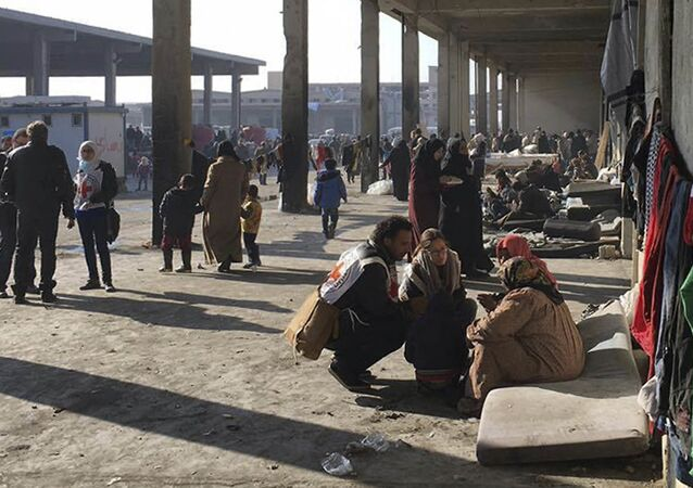 This image released by the International Committee for the Red Cross (ICRC) shows Syrians who were displaced with their families from eastern Aleppo gather at the collective shelter, in the village of Jibreen south of Aleppo, Syria, Monday, Dec. 12, 2016