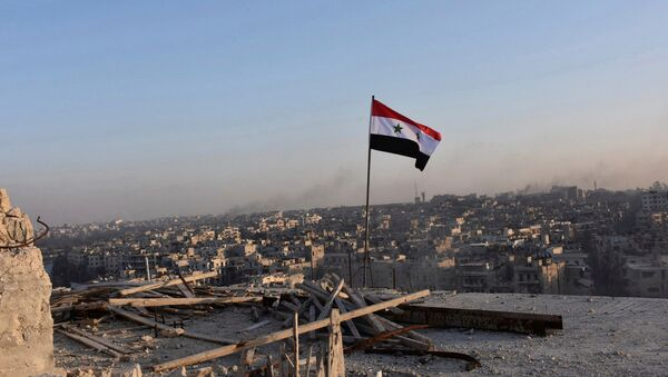 A Syrian national flag flutters near a general view of eastern Aleppo after Syrian government soldiers took control of al-Sakhour neigborhood in Aleppo, Syria in this handout picture provided by SANA on November 28, 2016. - Sputnik International
