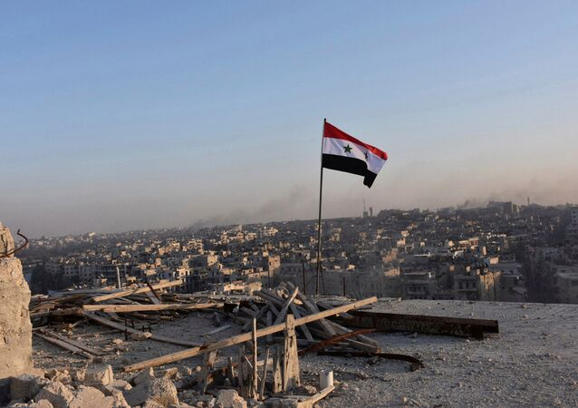 A Syrian national flag flutters near a general view of eastern Aleppo after Syrian government soldiers took control of al-Sakhour neigborhood in Aleppo, Syria in this handout picture provided by SANA on November 28, 2016.