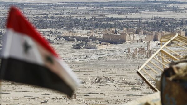 A Syrian national flag flutters as the ruins of the historic city of Palmyra are seen in the background, in Homs Governorate, Syria April 1, 2016. - Sputnik International