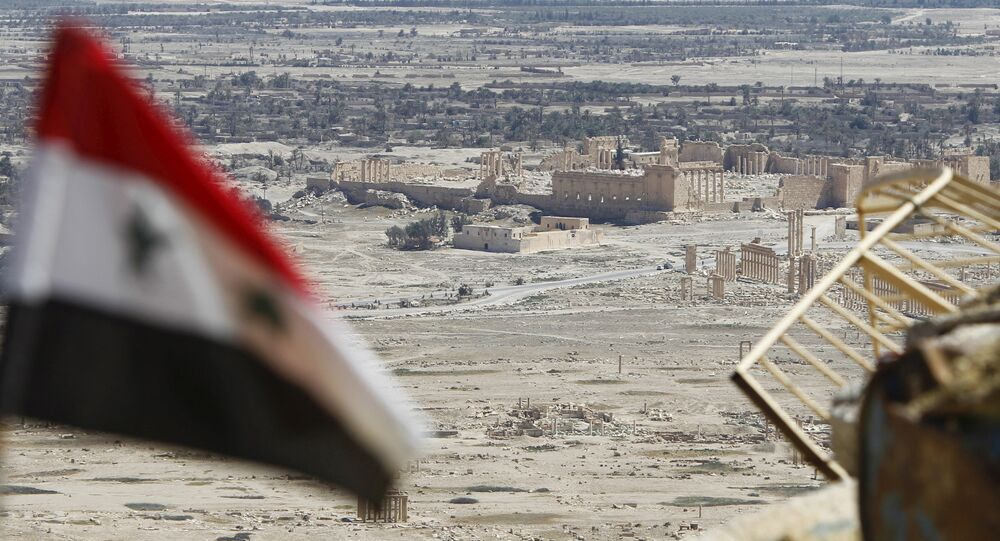 A Syrian national flag flutters as the ruins of the historic city of Palmyra are seen in the background, in Homs Governorate, Syria April 1, 2016.