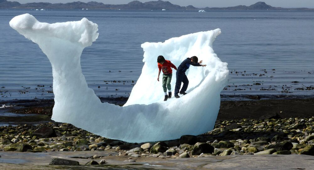 Children play amid icebergs on the beach in Nuuk, Greenland, June 5, 2016.