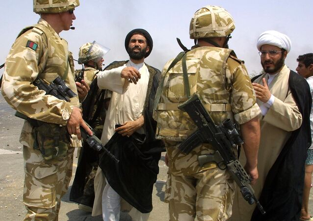 Iraqi clerks talk to British soldiers as clashes broke out in the southern city of Basra 09 August 2003 over fuel shortages and lack of electricity.
