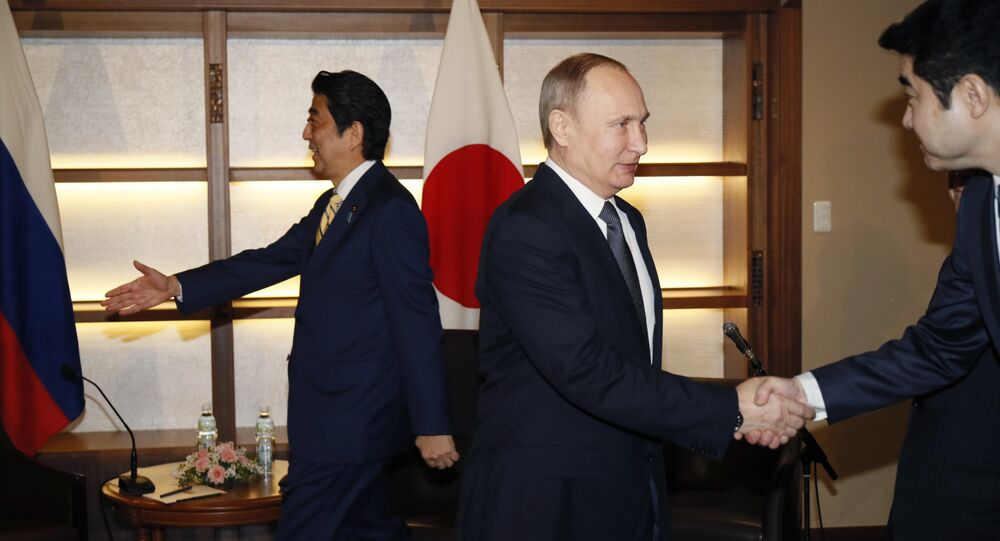 Russian President Vladimir Putin, center, shakes hands with a Japanese official as Japanese Prime Minister Shinzo Abe, left, prepares to greet a member of the Russian delegation during their meeting in Nagato, Japan, Thursday, Dec. 15, 2016.