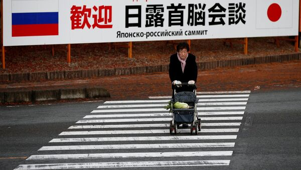 A woman walks in front of a sign board that reads Welcome Japan Russia summit meeting near a hot spring resort, the venue of the summit meeting between Japanese Prime Minister Shinzo Abe and Russian President Vladimir Putin, in Nagato, Yamaguchi prefecture, Japan, December 15, 2016. - Sputnik International