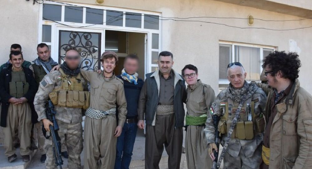Backpackers Will Meara and Craig Reynolds pose with peshmerga fighters along the frontlines in the fight against Daesh.