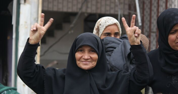 Woman in Hanano, East Aleppo celebrates the SAA liberation of the district from Nusra Front occupation