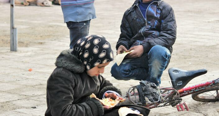 Child eating food being provided by the Syrian Government and Russia humanitarian organisations. Hanano, East Aleppo