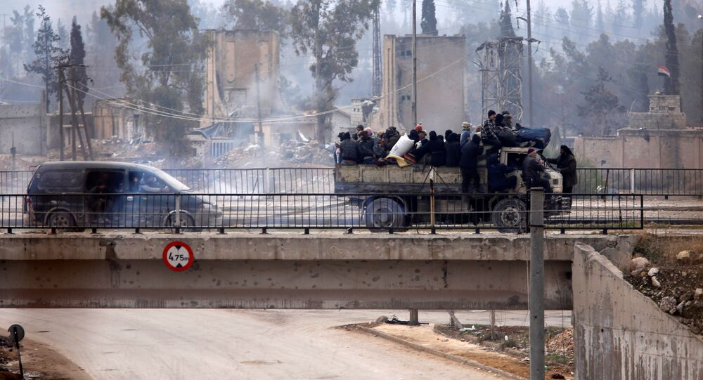 Evacuees from rebel-held eastern Aleppo ride on pick-up trucks along the government-held area of al-Ramousah bridge, Syria December 16, 2016.