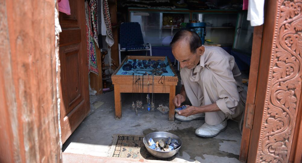 A shopkeeper polishes gemstones at his shop in Karimabad town of northern Hunza valley