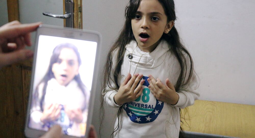 Syrian Bana al-Abed is filmed by her mother as they prepare to post on Twitter in English about life in the besieged eastern districts of Syria's Aleppo, on October 12, 2016.