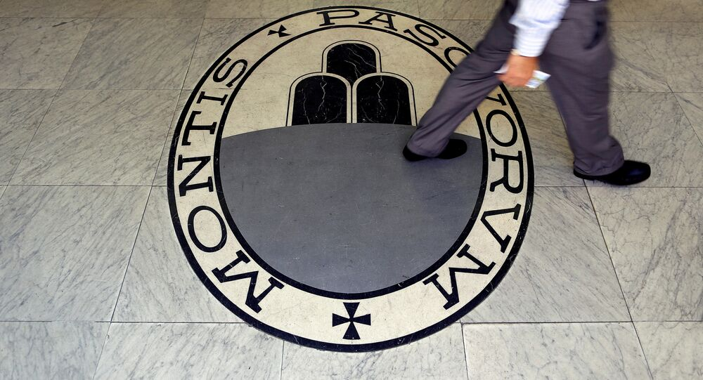 A man walks on a logo of the Monte Dei Paschi Di Siena bank in Rome, Italy, September 24, 2013.