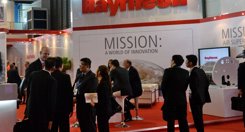 Trade visitors stand in front of a Raytheon booth during the Singapore Air Show. (File)