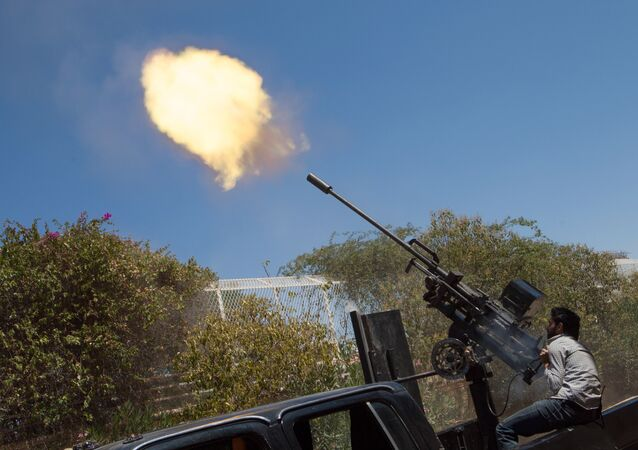 A rebel fighter fires a 23mm anti-aircraft gun from the back of a pick-up truck as a Syrian Airforce plane flies overhead during clashes between the rebels and pro-government troops on the outskirts of the northern city of Aleppo