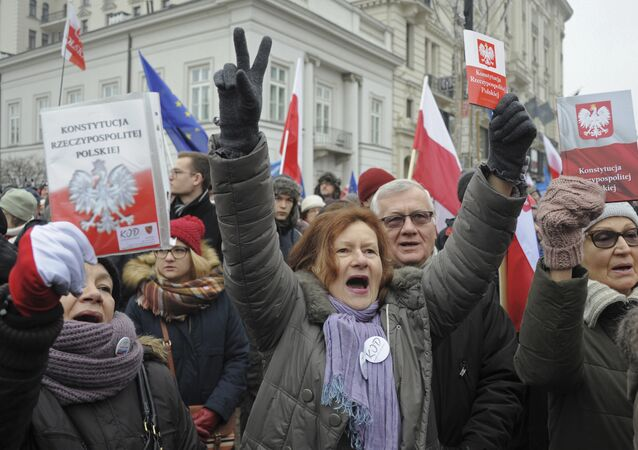 Protesters holding copies of Poland's constitution shout slogans during an anti-government demonstration, in Warsaw, Poland