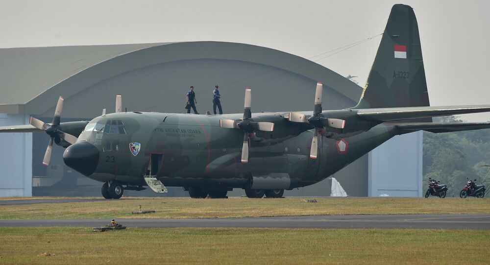 This picture taken on July 1, 2015 shows personnel on top an Indonesia Air Force C-130 Hercules aircraft parked on the tarmac at Halim Air Base in Jakarta