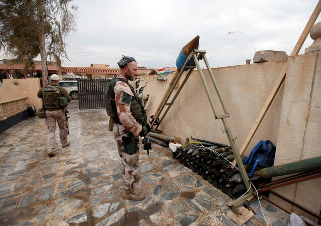 A US soldier looks at weapons and ammunition belonging to Daesh terrorists in the town of Bashiqa, east of Mosul, Iraq, December 14, 2016