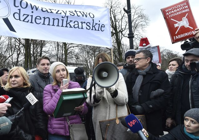 In this Thursday, Dec. 15, 2016 photo a protester raises a communist-era sign reading Photographing Forbidden, during a journalists protest in front of the parliament in Warsaw, Poland, against the ruling Law and Justice party plans to impose new rules starting Jan. 1 that would drastically limit reporters' access in parliament