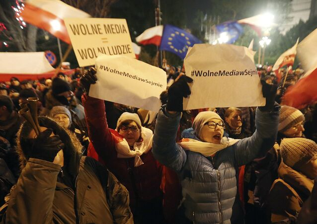 People gather to demonstrate outside the Parliament building in Warsaw, Poland, on Friday Dec. 16, 2016, in support of opposition lawmakers protesting against the ruling party's plans to limit media access to lawmakers