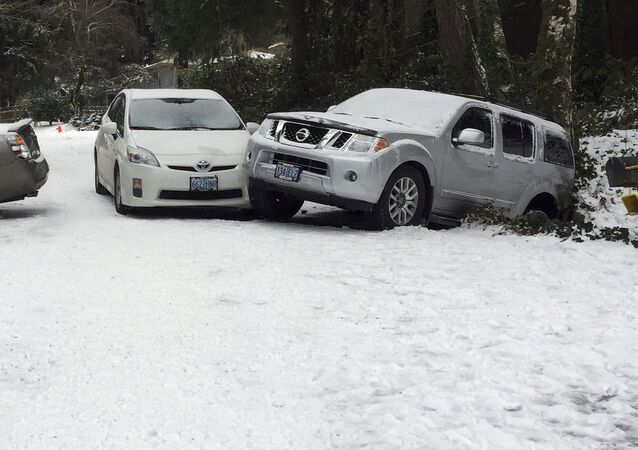 Cars, involved in a slippery accident after last nights' snow storm are strewn across a street in Lake Oswego, Ore., Thursday, Dec. 15, 2016