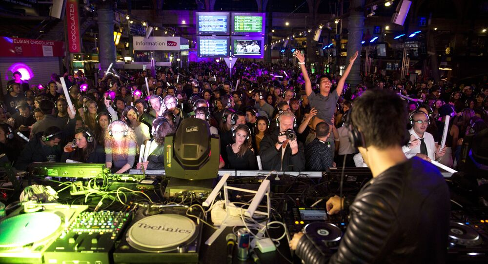 People dance as they listen to music using wireless headphones at a silent disco set up in the Gare du Nord railway station in Paris early on October 4, 2015, during the Nuit Blanche night-time arts festival