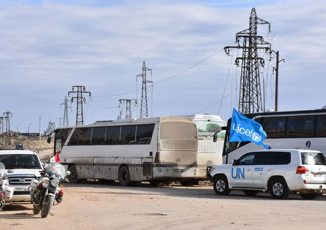 A vehicle from the United Nations drives through the Syrian government-controlled crossing of Ramoussa, on the southern outskirts of Aleppo, on December 18, 2016, during an evacuation operation of rebel fighters and civilians from rebel-held areas