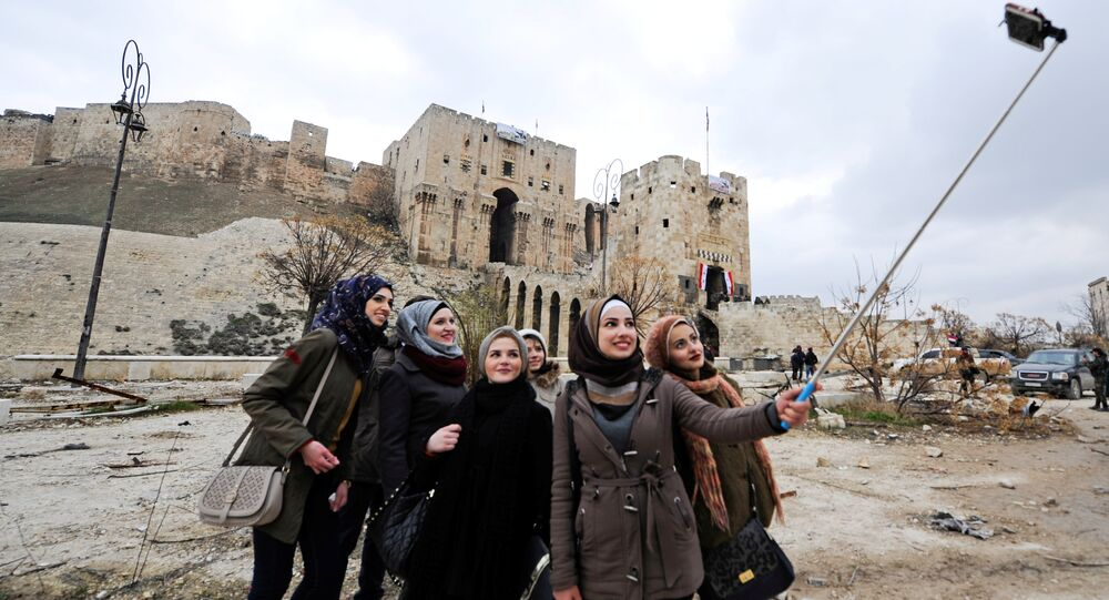 Women take a selfie outside Aleppo's historic citadel, in the government controlled area of the city, Syria December 17, 2016