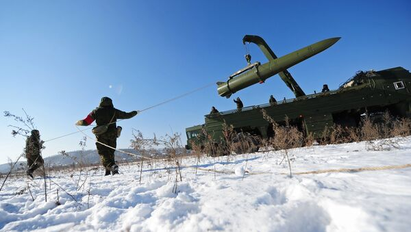 Russian soldiers watch a transporter-loader place an Iskander-M shorter-range missile onto a launcher during an exercise - Sputnik International