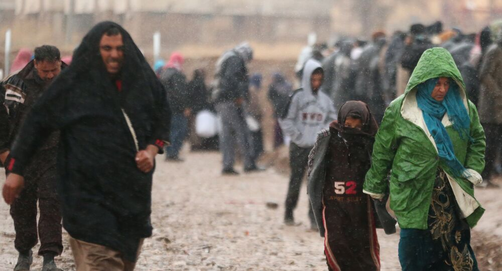 Displaced Iraqis, who fled the Islamic State stronghold of Mosul, walk under rain in Khazer camp, Iraq December 14, 2016