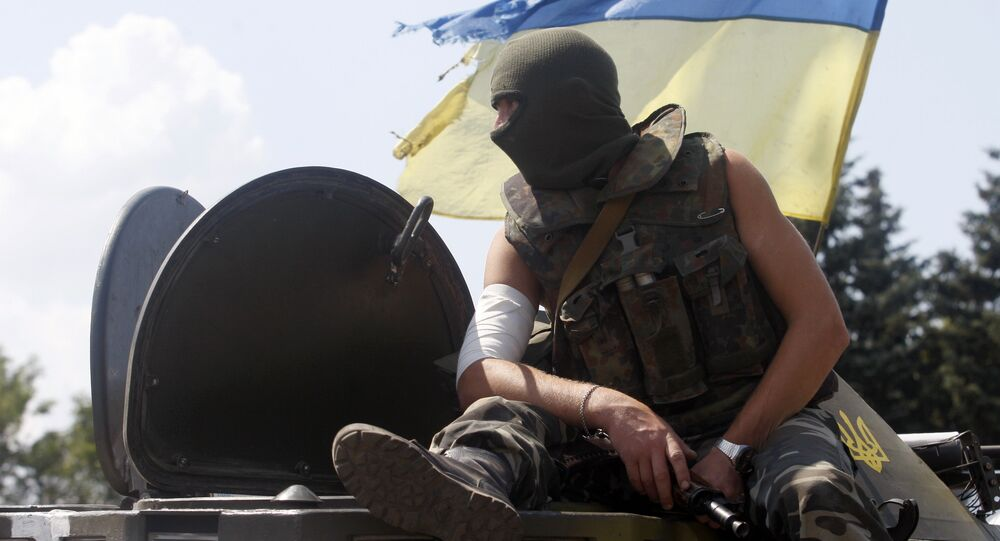 An Ukrainian soldier sits on the top of an APC at a checkpoint in the eastern city of Debaltsevo. File photo